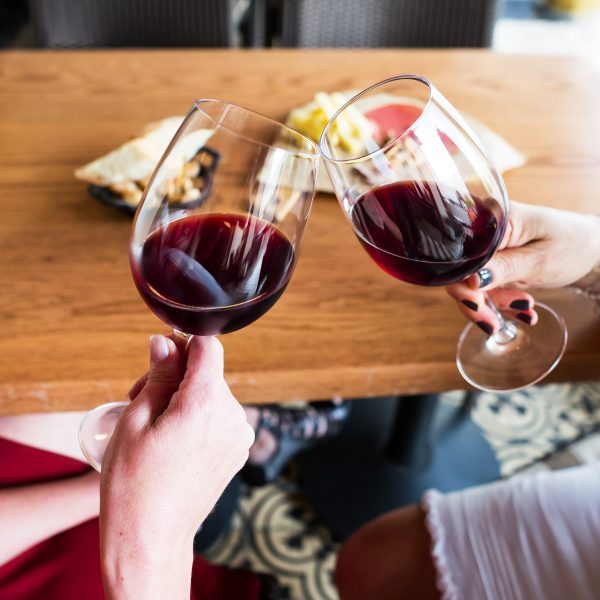 Image of two wine glasses filled with wine toasting