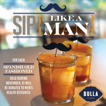 TWO OLD FASHION COCKTAILS WITH A MUSTACHE GARNISH & ORANGE PEEL DESCRIBING SIP LIKE A MAN TO DONATE TO MEN'S HEALTH RESEARCH